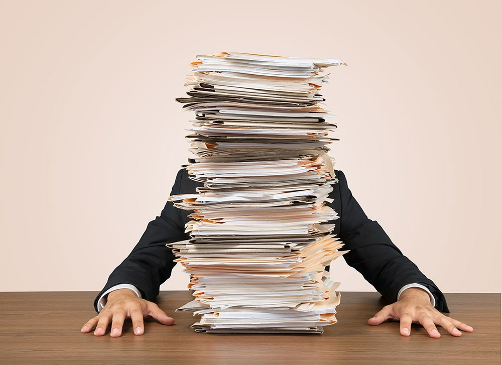 Person behind a stack of documents
